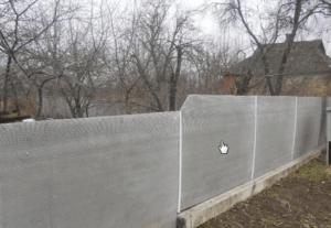 Забор выполнен из плоского шифера