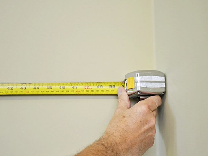 Измерение стены рулеткой